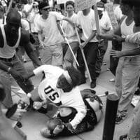 Black woman protecting a fallen racist from a crowd