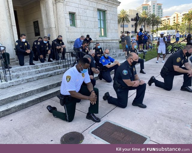 The police taking a knee with protesters in Miami, Florida