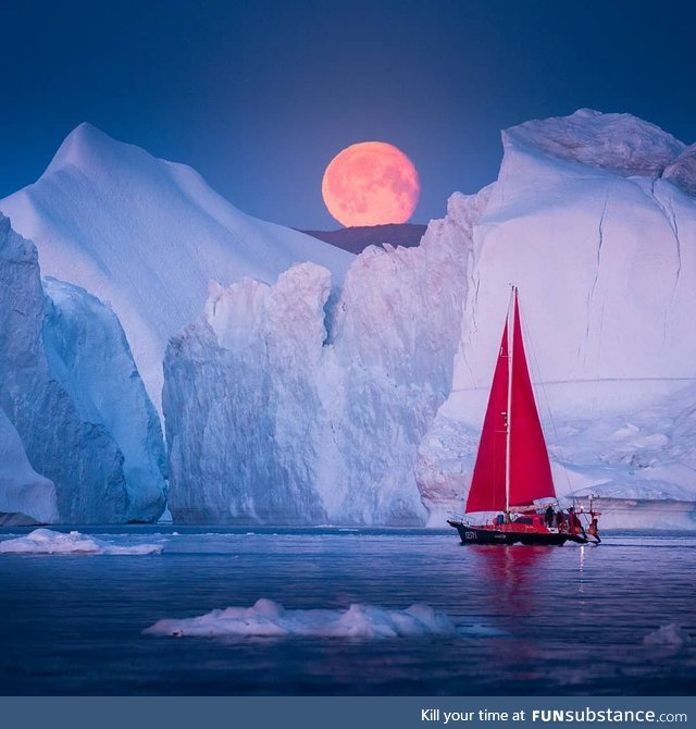 A sailboat passing under a blood moon in Greenland