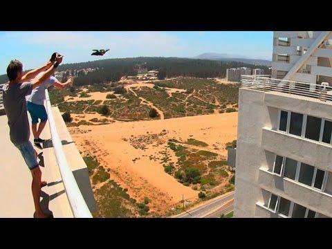 Insane man flies through a narrow gap between two buildings
