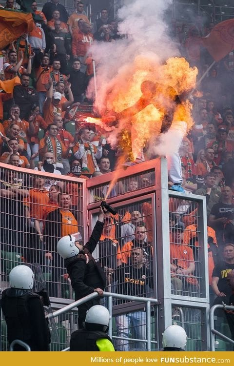 A Soccer fan, armed with a flare, was sprayed by police to prevent him from climbing over
