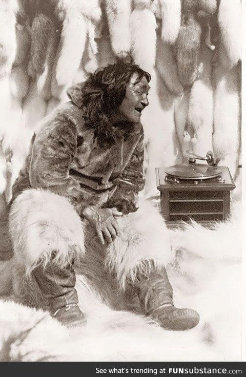 An Eskimo man enjoying some music on a record player in 1922