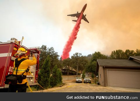 """An air tanker drops fire retardant on flames as firefighters continue to battle"