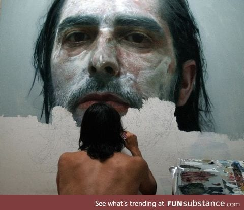 Artist paints photorealistic portrait of himself covered in paint