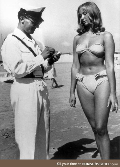 Woman receives ticket for illegally wearing a bikini on a beach. (Italy, circa 1957)