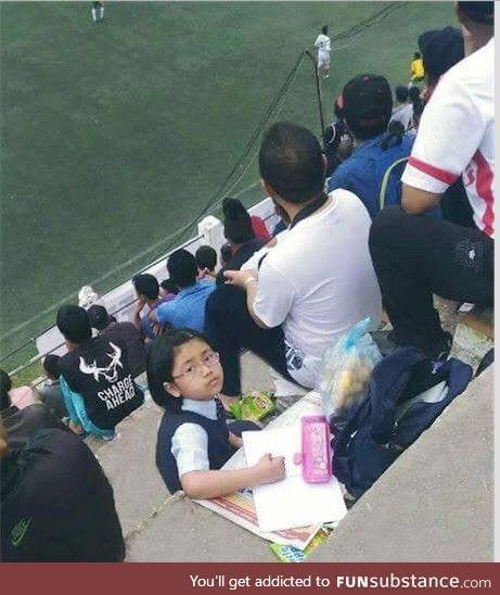 Daddy enjoys a football match while kiddo does homework. (Mizoram, India)