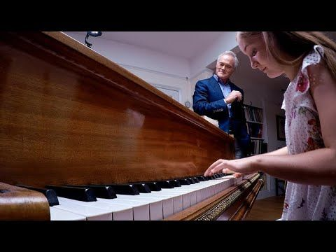 Girl performs an improvised piece on the piano using four randomly picked notes