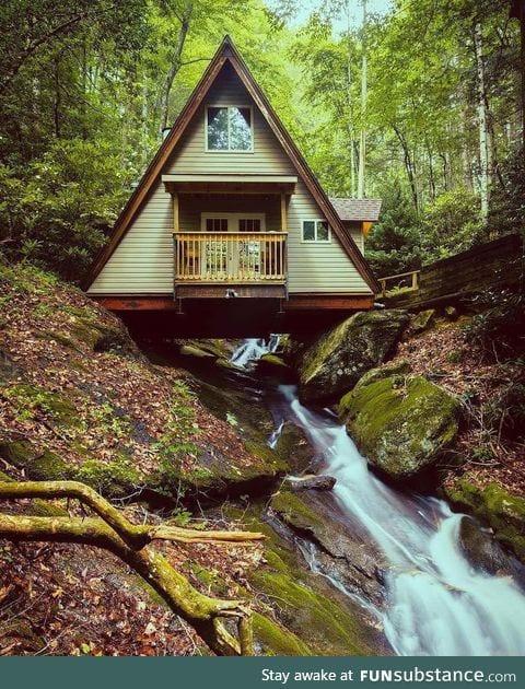 A-frame cabin built over a creek