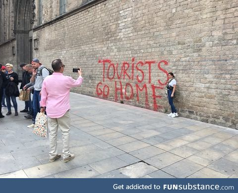 """Tourists taking a picture in front of a """"Tourists go home"""" graffiti in Barcelona"""
