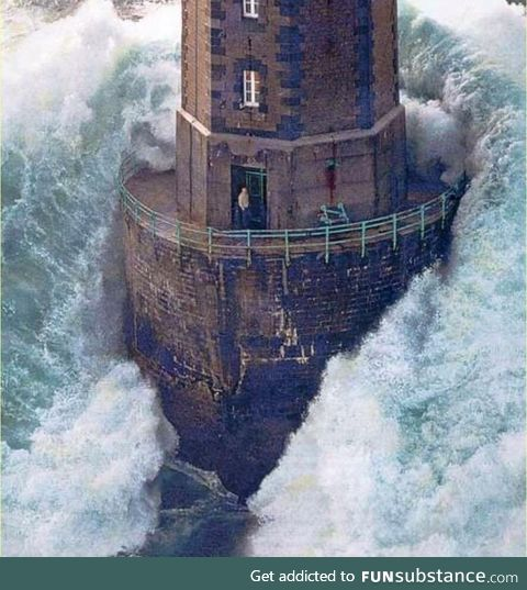 A massive wave hits a lighthouse off the coast of France