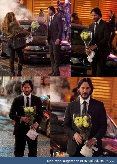 Keanu Reeves getting flowers from a fan