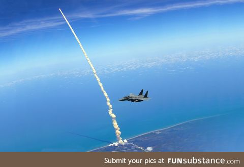 An F-15E patrols Kennedy Space Center as the Space Shuttle Atlantis launches