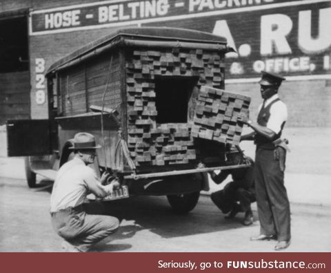 "[1926] Federal agents, alerted by the smell of alcohol, inspecting a ""lumber truck"""