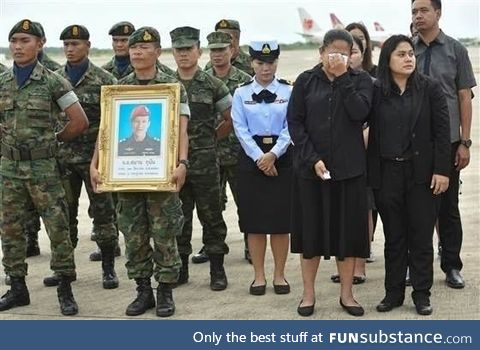 An honor guard holds up a picture of Samarn Kunan, 38, a diver who died working to save