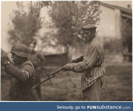 Jewish prisoner, recently liberated from a concentration camp, aiming a gun at a nazi