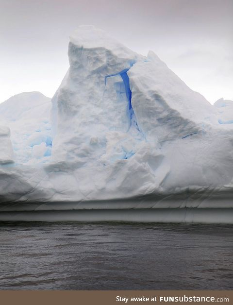 A bright brilliant blue glows from within an Antarctic iceberg
