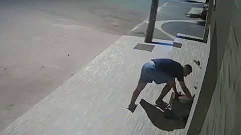 Man walks down the street and sees a homeless dog trying to sleep.