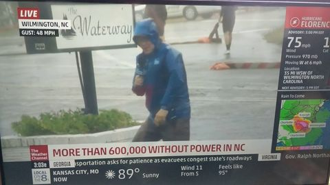 Reporter plays up the hurricane while two dudes casually walk in the background