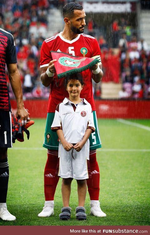 Moroccan soccer team captain Benatia covering a little girl's head from the rain
