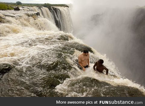 Two guys sitting near the edge of the Devil's Pool, Victoria Falls, Zambia