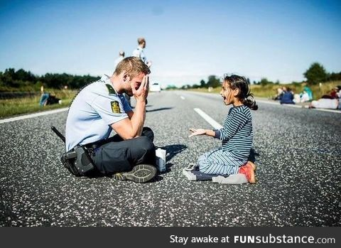 A Danish officer playing with a Syrian refugee