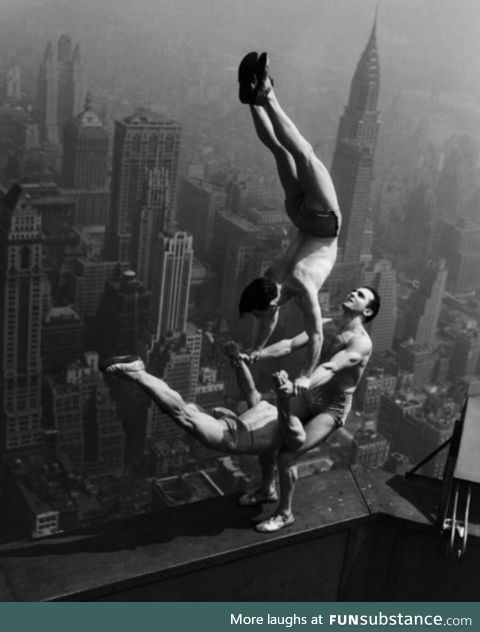Acrobats balance at the top of Empire State Building, 1934