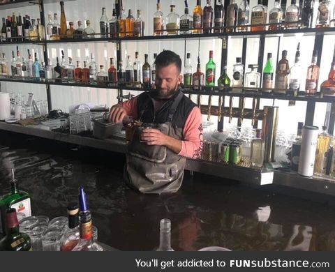 Owner pouring himself a drink after the rising Mississippi engulfed his bar in Davenport,