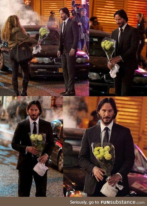 Keanu Reeves getting flowers from a fan on set of John Wick 2