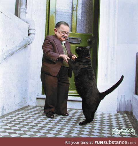 Henry Behrens, the smallest man in the world dances with his pet cat in the doorway of