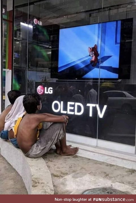 Shop owner in India playing cartoons on storefront display TV for kids to watch