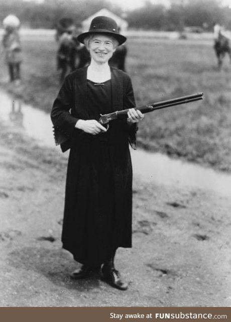 Annie Oakley holding a gun that Buffalo Bill gave her, 1922.