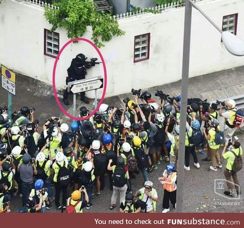 Police Officer (encircled) Surrounded by Photographers in Hong Kong