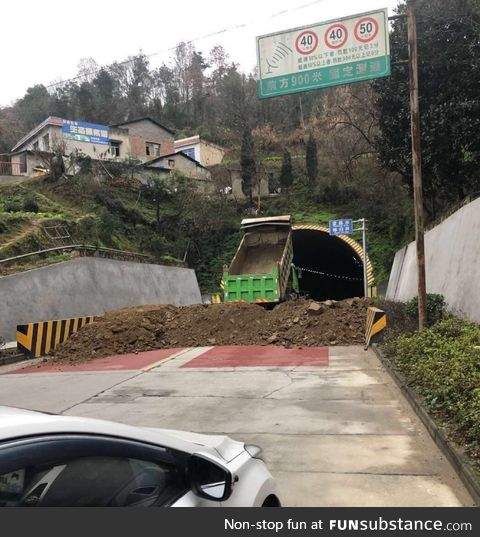 Wuhan, China city officials use dirt to block roads