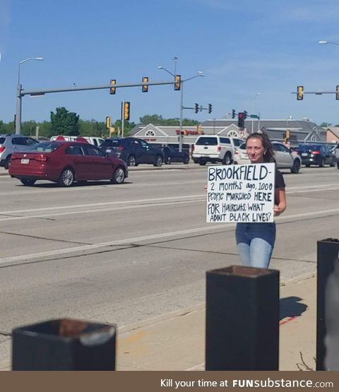 Young woman at Wisconsin protest calls out her city with this sign