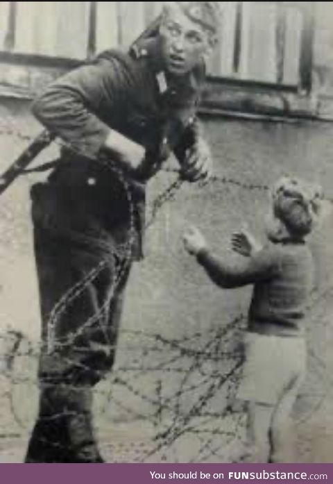 East German soldier letting boy through to reunite with his family