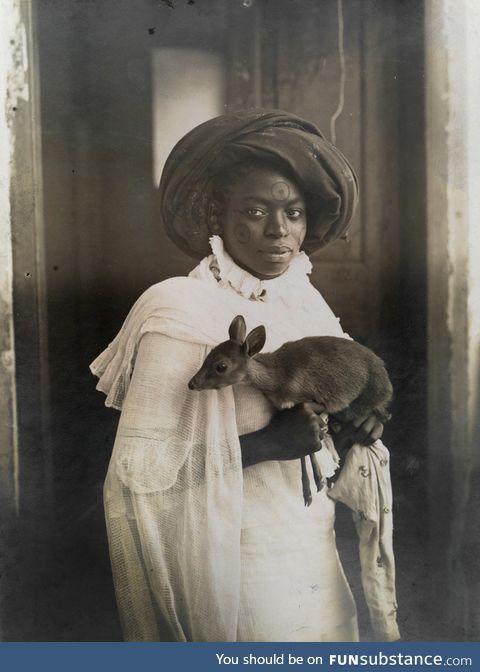 A photogenic Kenyan woman holding her pet deer in Mombassa, 1909