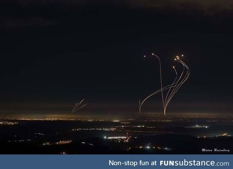 Rockets shot from Gaza (left) are met with intercepting rockets from the Iron Dome
