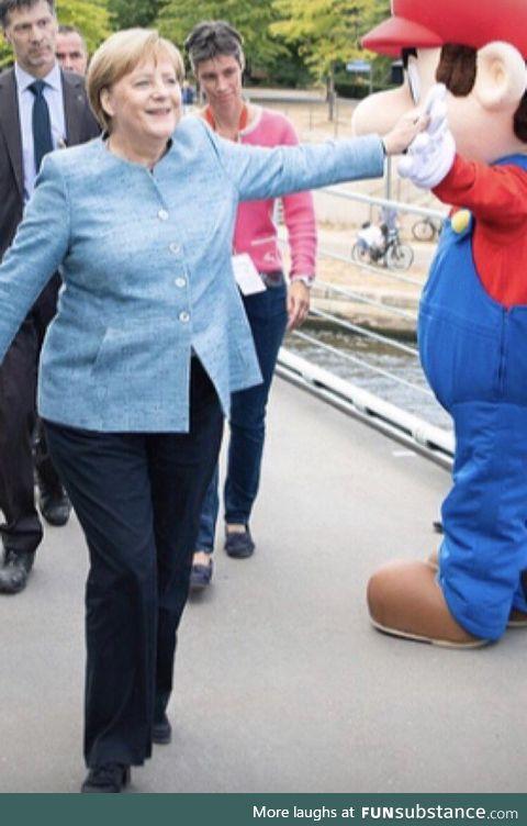 Chancellor Merkel casually high fiving Mario