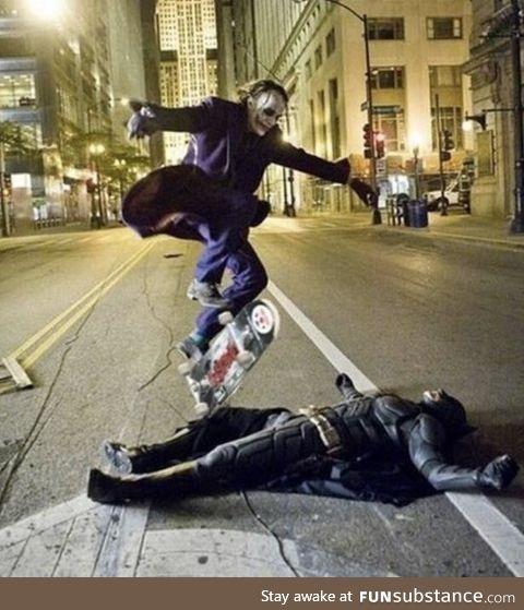 Heath ledger as the joker skateboarding over Christian bale as Batman. During a break