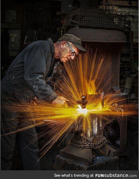 Blacksmith striking his hammer