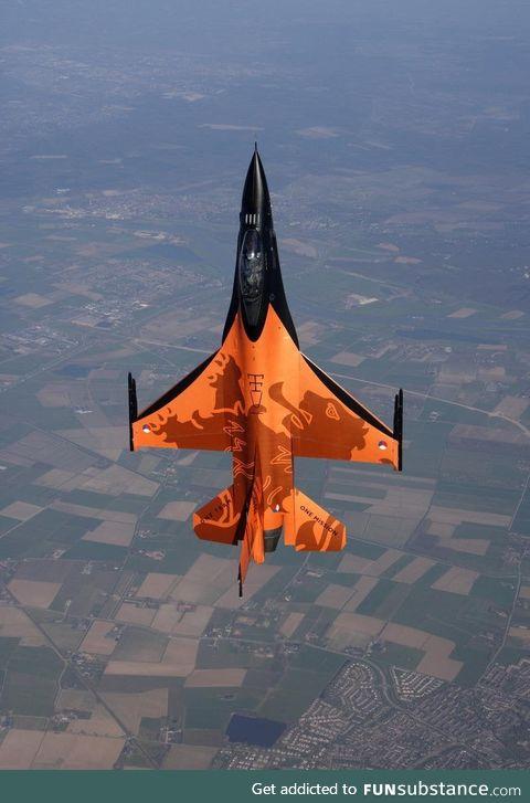 A Dutch F-16 Falcon above a typical Dutch landscape