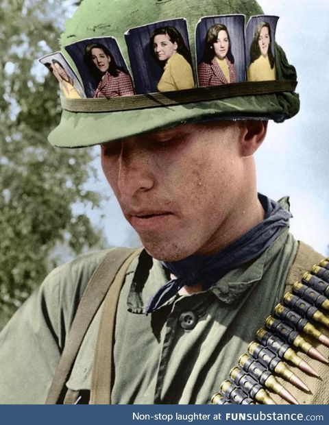 US soldier with pictures of his girlfriend, Chu Chi base camp, Vietnam 1968